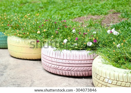 DIY idea to recycle of tire used with flowers or plant in old rubber painted pastel color in garden home, low angle view.