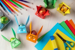 DIY paper crafts for the Easter holiday. Origami paper Easter bunny - egg basket for Easter greetings. Hobbies at home. Self-employment and needlework. DIY concept. Step by step instruction