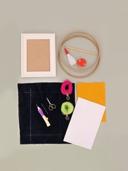 DIY project equipments for a handmade frame decoration including a wooden hoop, white frame, piece of fabric, punch needle, wools, glue and papers, top view concept of leisure time tools