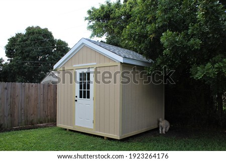 DIY project model backyard tool shed with a dog outside in a yard. Many trees are surrounding the shed.