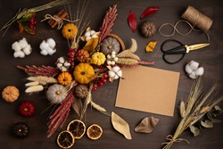 Diy rustic autumn table decoration. Floral interior decor for fall holidays with handmade pumpkins. Flatlay, top view