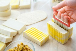 Diy soap cutting process. Craft soap making process with herbs and flowers. hobby eco artisan handmade soap on white table. Many various white yellow homemade bar soaps