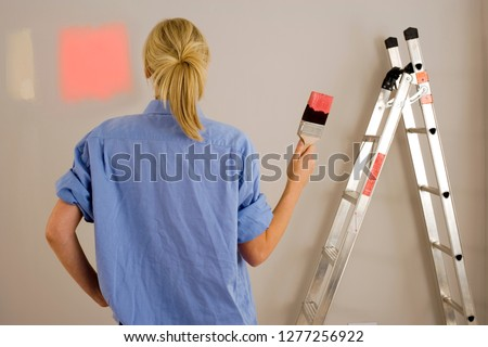 Diy woman decorating at home painting wall with test swatches holding paintbrush dipped in red paint