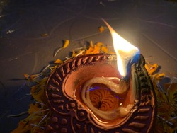 Diya lamp with fire. Traditional Divali festival. Close up