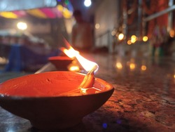 Diya lamp with fire. Traditional Divali festival. Close up in a row in festive season