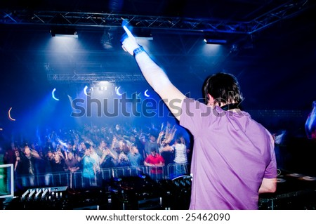 Dj at the concert, blurred crowd on background