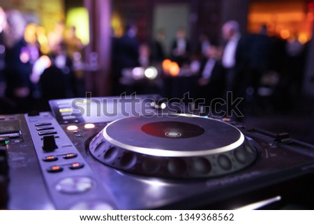 DJ console mixer at a nightclub. The disco, Banquet, people blurred background dancing.