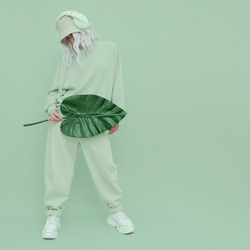 Dj Girl posing in studio. Urban style. Fresh casual mint outfit. Fashion monochrome aesthetic colours.  Bio palm tropical mood