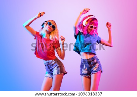 DJ Girl with Pink Blond Fashion Hairstyle Dance. Two Young Playful Hipster in Trendy Headphones. Sexy Woman in Sunglasses. Music vibrations, Night Clubbing. Creative Art Bright Light