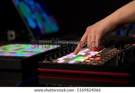 Dj hand remixing music on midi controller #1169824066