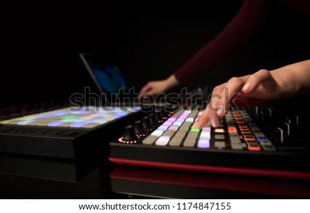 Dj hand remixing music on midi controller #1174847155