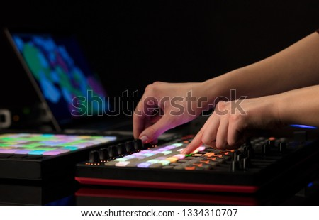 Dj hand remixing music on midi controller #1334310707