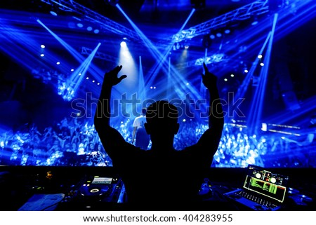 DJ hands up at night club party under blue light with crowd of people