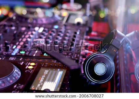 DJ headphones on controller turntable console mixing desk at stage in the night club, music beach party festiva and nightlife concept. Сток-фото ©
