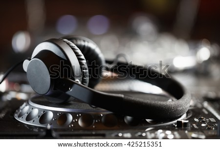Dj headphones on turntable player.Professional stage audio equipment in nightclub.Techno music party background.Play musical tracks on nightclub dance party