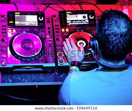Dj in headphones mixes the track in the nightclub at party