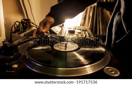 Dj in studio puts needle on record