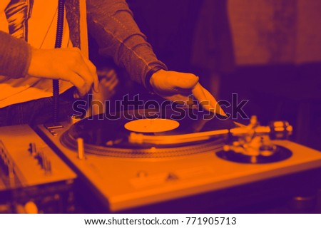 Dj mix tracks at party on vinyl record player. The Duotone effect - orange and purple