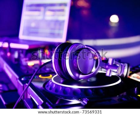 Dj mixer with headphones at a nightclub #73569331