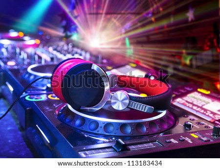Dj mixer with headphones at nightclub.  In the background laser light show