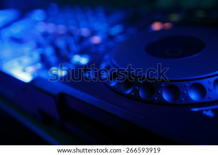 DJ mixer with light colored spotlights discos, shallow depth of field and beautiful swirling bokeh