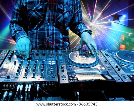 Dj mixes the track in the nightclub at a party. In the background laser light show
