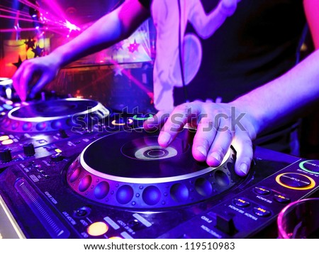 Dj mixes the track in the nightclub at party. In the background laser light show