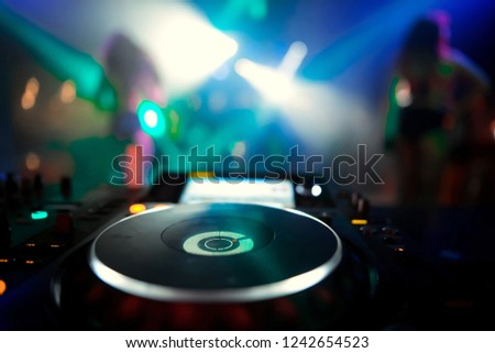 Dj mixes the track in the nightclub at party. Top view