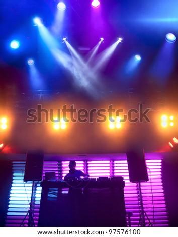 DJ mixes track at nightclub on scene. Bright beautiful lighting