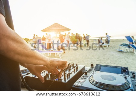 Dj mixing at sunset beach party in summer vacation - Disc jockey hands playing music for tourist people in chiringuito bar - Music and fun concept - Focus on right hand - Tilted horizon composition