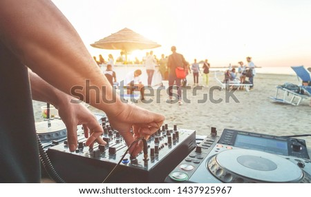 Dj mixing at sunset beach party in summer vacation outdoor - Disc jockey hands playing music for tourist people in chiringuito kiosk bar - Event, music and fun concept - Focus on right hand