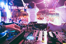 Dj mixing outdoor at beach party festival outdoor with crowd of people in background - Soft focus on left hand - Fun, summer, youth, nightlife, music, nightclubs and entertainment concept