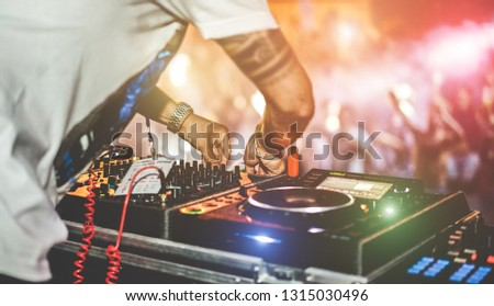 Dj mixing outdoor at beach party festival with crowd of people in background - Summer nightlife view of disco club outside - Soft focus on right hand - Fun ,youth,entertainment and fest concept