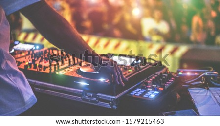 Dj mixing outdoor at new year party festival with crowd of people in background - Nightlife view of disco club outside - Soft focus on bracelet - Fun ,youth,entertainment and fest concept Сток-фото ©
