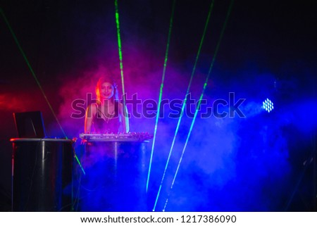 DJ Party Playing Mixing and Mastering Electronic Dance Music with electro light effects and lights #1217386090