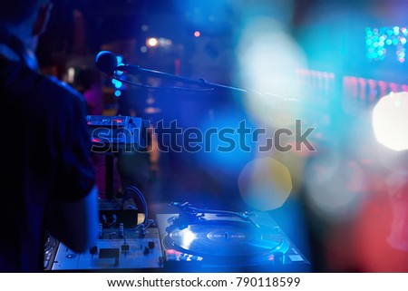 DJ performs in a nightclub at a party. Beautiful blurry colored bokeh from the lights of searchlights and illuminators.