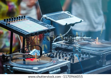 Dj place on party.Professional disc jockey setup on outdoor festival. Retro vinyl turntable player with analog disc,digital midi controller,sound mixer and laptop for playing musical tracks #1170966055