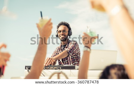 Dj playing at the beach party. Concert outdoor, with people raising drinks and hands to the sky. Entertainment and people concept