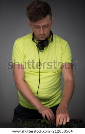 DJ playing music. Confident young DJ with stylish haircut and headphones at work spinning on mixer looking down while standing isolated on dark background