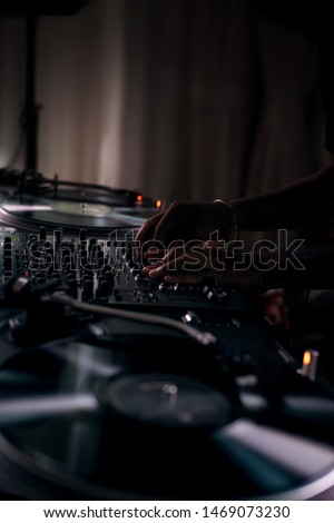 DJ playing music from vinyl on afterparty. Mixing House, Techno and Electronic Music. Dj's hands and sound equipment. Professional disc jockey.