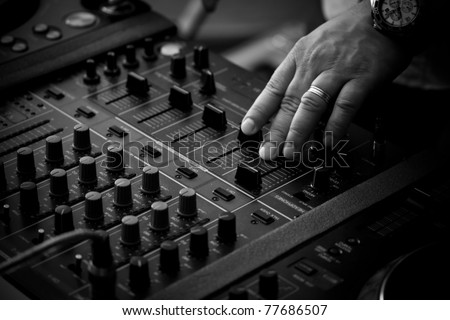 DJ playing music on professional mixing controller - stock photo