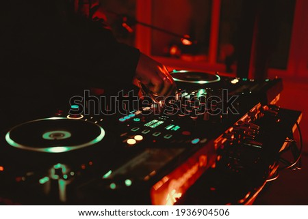 Dj playing music on rave party in nightclub.Professional disc jockey plays concert turntables,sound mixer devices on stage in dark night club.Royalty free curated collection with parties and concerts