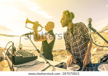 Dj playing summer hits at sunset beach party with trumpet jazz performer - Vacation concept at open air club with house music groove location - Warm vintage sunshine filter with backlight soft focus