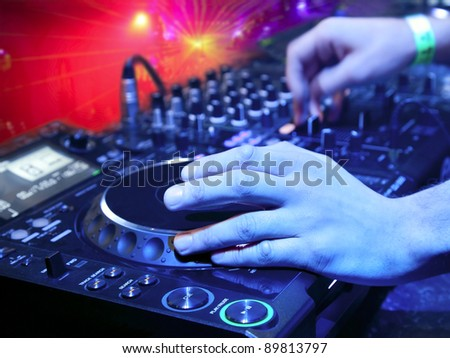 Dj playing the track in the nightclub at a party. In the background laser light show