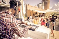 Dj playing trendy music in a open air club - People dancing and partying while the disc jockey mixes two song tracks in the console at a summer concert