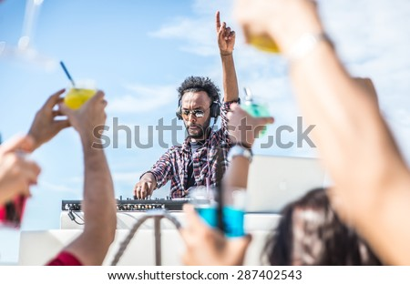 dj set at the beach party. dj spins the music and people is excited with hands up. concept about party, music and people