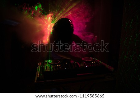 DJ Spinning, Mixing, and Scratching in a Night Club, Hands of dj tweak various track controls on dj's deck, strobe lights and fog, or Dj mixes the track in the nightclub at party. Selective focus