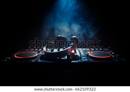 DJ Spinning, Mixing, and Scratching in a Night Club, Hands of dj various track controls on dj's deck, strobe lights and fog, selective focus, close up