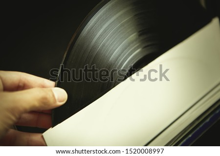 Dj takes vinyl record out of paper sleeve.Old analog audio equipment.Vintage turn table records collection.Retro disc jockey gear in closeup.Play and listen music in hi-fi quality on turntables player