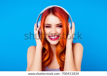 Stock Photo Dj turn on the music! Red head ginger young and very pretty girl is listening to music in big white earphones. Her smile is beaming, she is happy
